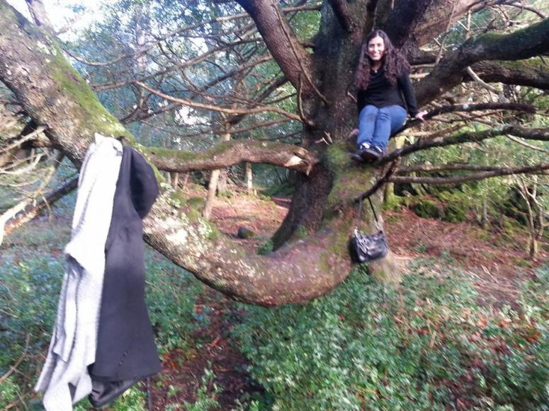 My friend climbing a tree and using it as a coat hanger with no fear